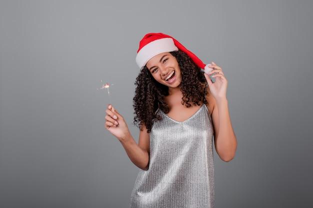 Feliz chica negra con brillantes bengalas con sombrero de navidad y vestido aislado en gris