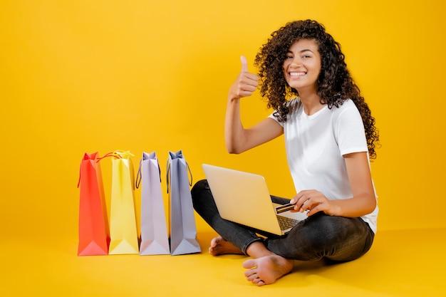 Feliz chica negra con coloridos bolsos de compras sentado con laptop y tarjeta de crédito aislado sobre amarillo