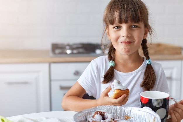 Feliz chica optimista positiva con lindas coletas sentado en la mesa en la cocina y sosteniendo la hornada dulce en las manos y la taza con bebida, disfrutando de un delicioso postre, mirando a la cámara.