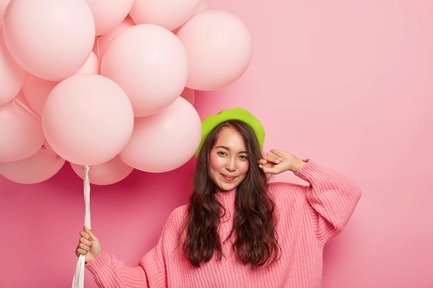Feliz chica oriental de pelo oscuro sostiene un montón de globos de aire, viste boina verde y suéter de gran tamaño