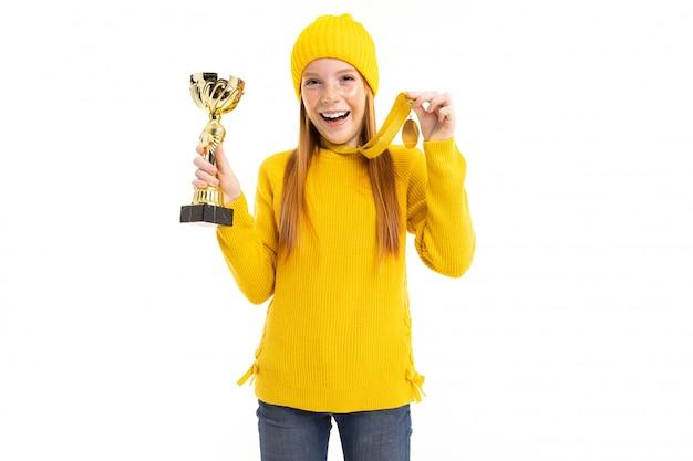 Feliz chica pelirroja sosteniendo una copa y una medalla de oro sobre fondo blanco.
