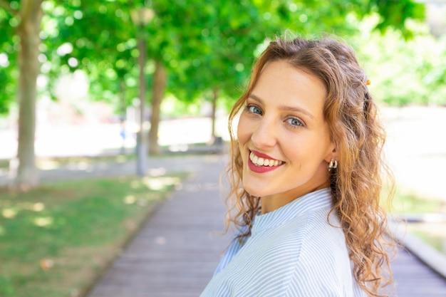 Feliz chica de pelo ondulado sonriendo a la cámara al aire libre