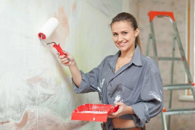 Feliz chica pinta la pared