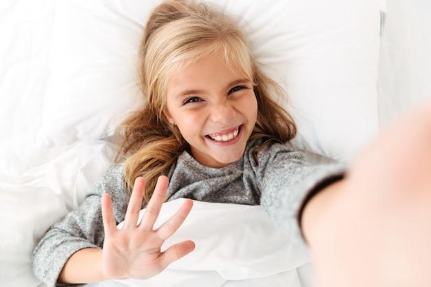 Feliz chica rubia sonriente tomando selfie mientras está acostado en la cama