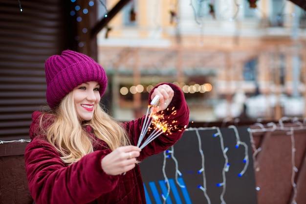 Feliz chica rubia vestida con ropa elegante, prende fuego a bengalas en la feria de navidad en kiev
