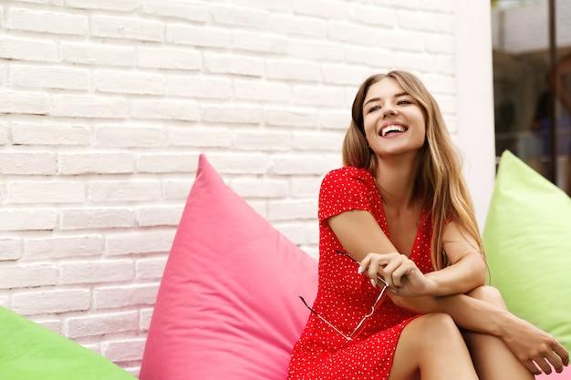 Feliz chica rubia en vestido rojo sentado en un puf junto a la pared blanca