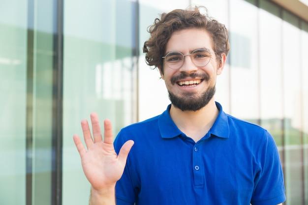 Feliz chico amable con gafas, saludando hola