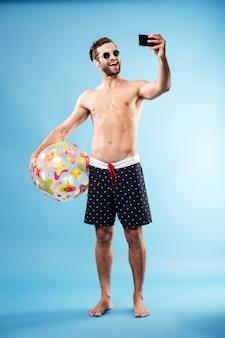 Feliz chico sin camisa con pelota de playa y haciendo selfie