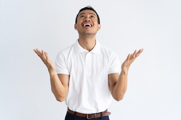 Feliz chico emocionado rezando por agradecer a dios
