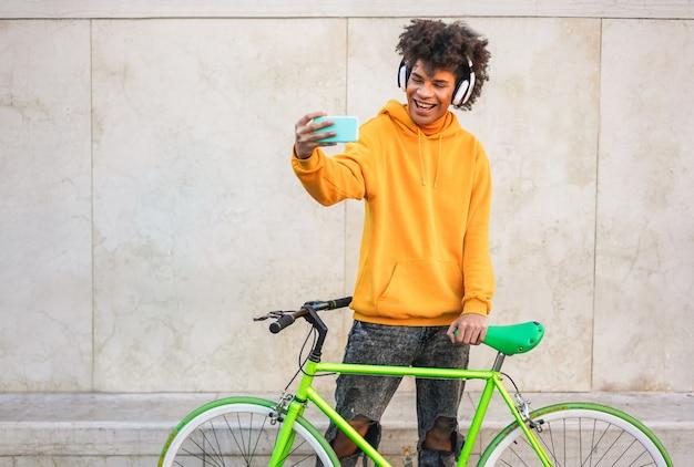 Feliz chico milenario africano haciendo video historia mientras escucha música playlist con smartphone al aire libre
