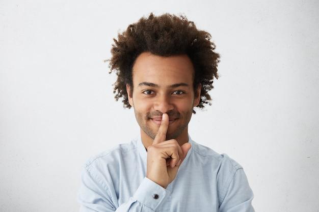 Feliz chico de piel oscura con peinado africano con elegante camisa blanca que muestra el signo de silencio