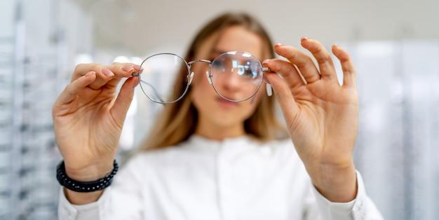 Feliz cliente u óptica está de pie con un conjunto de gafas