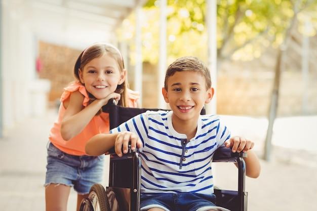 Feliz colegiala de pie con colegial en silla de ruedas