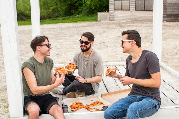 Feliz compañía charlando y comiendo pizza en picnic