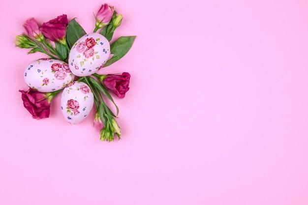 Feliz concepto de pascua. flores de primavera rosa con huevo de pascua con estampado de flores sobre fondo rosa de diseño