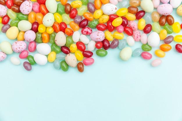 Feliz concepto de pascua. preparación para vacaciones. huevos de chocolate de caramelo de pascua y dulces de gelatina aislados sobre fondo azul pastel de moda. minimalismo simple, plano, vista superior, espacio de copia.
