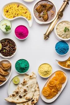 Feliz concepto sagrado mostrando comida india variada para el almuerzo como pollo paneer mantequilla masala naan jeera arroz chana negro freír jalebi ras malai thandai y farsan con colores holi y pichkari