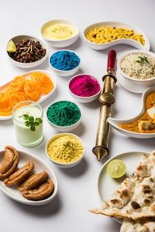 Feliz concepto sagrado que muestra comida india variada para el almuerzo como mantequilla paneer masala naan jeera arroz chana negro freír jalebi ras malai thandai y farsan con colores holi y pichkari