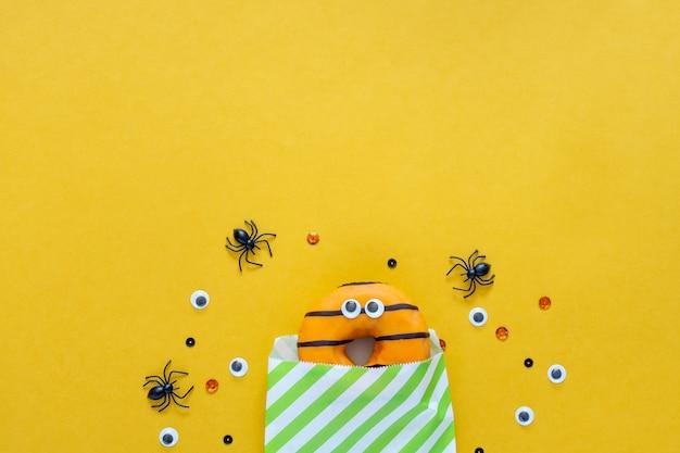 Feliz concepto de vacaciones de halloween. comida divertida para niños: rosquillas asustadas en bolsa de papel sobre fondo amarillo brillante con araña negra y ojos. tarjeta de felicitación de fiesta de halloween. endecha plana, vista superior, arriba.