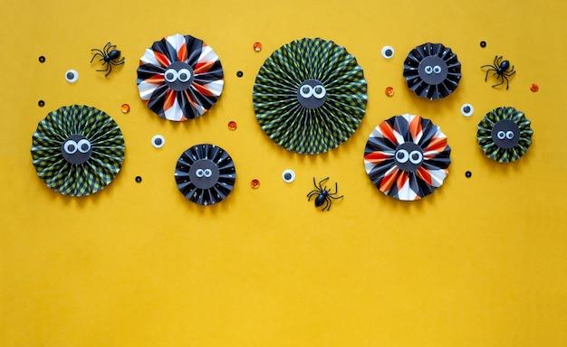 Feliz concepto de vacaciones de halloween. decoraciones de papel de bricolaje sobre fondo amarillo brillante. maqueta de tarjeta de felicitación de fiesta de halloween con espacio de copia. endecha plana, vista superior, arriba.
