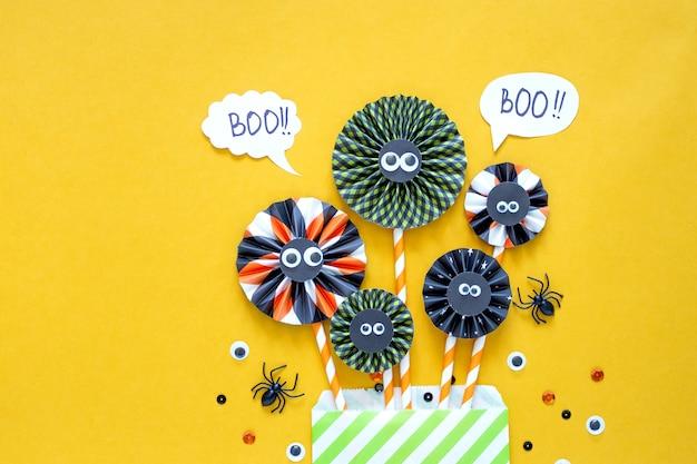 Feliz concepto de vacaciones de halloween. decoraciones de papel de bricolaje sobre fondo amarillo brillante. tarjeta de felicitación de fiesta de halloween. endecha plana, vista superior, arriba.