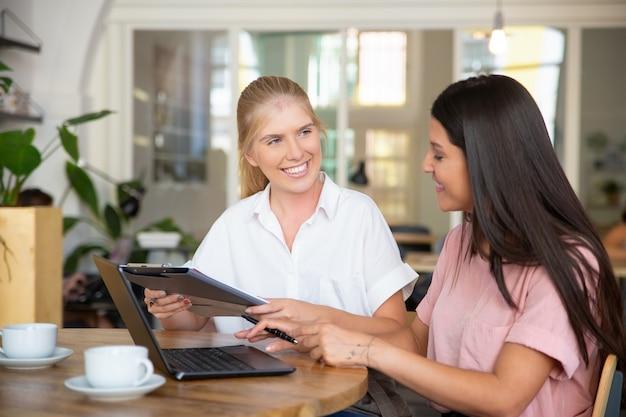 Feliz confiado agente y cliente reuniéndose con una taza de café y firmando un acuerdo