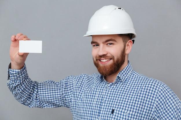 Feliz constructor barbudo con tarjeta en blanco