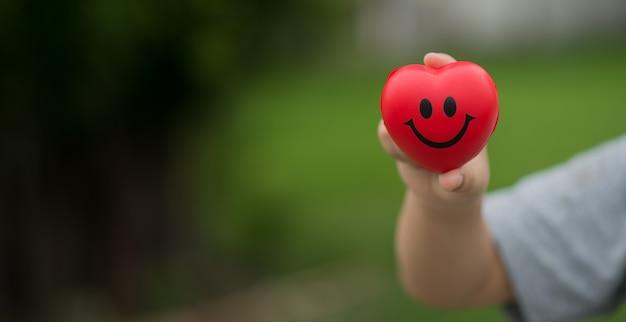 Feliz corazón rojo en la mano del niño