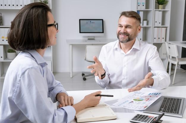Feliz corredor maduro y su joven colega discutiendo documentos financieros en la oficina