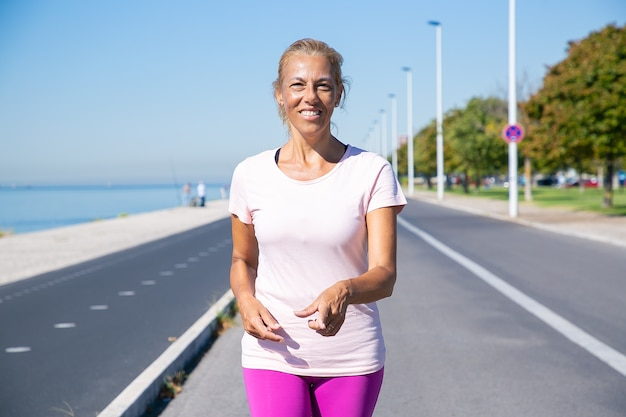 Feliz corredor de mujeres maduras caminando por la pista de atletismo en el río, mirando y señalando con el dedo. vista frontal. concepto de actividad y edad