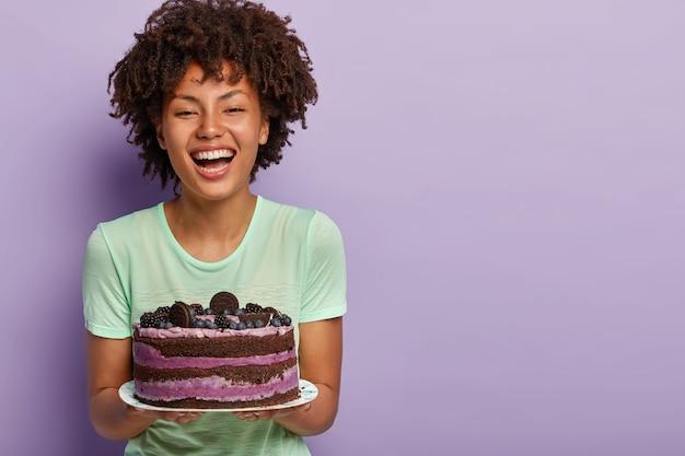 Feliz cumpleañera se ríe alegremente, sostiene un gran pastel de frutas sabroso, le gusta comer alimentos dulces, mejora el estado de ánimo elevando el azúcar en sangre