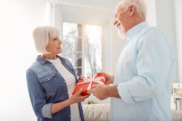 Feliz cumpleaños. agradable anciana dando a su esposo un regalo de cumpleaños bellamente envuelto mientras él lo acepta con una amplia sonrisa