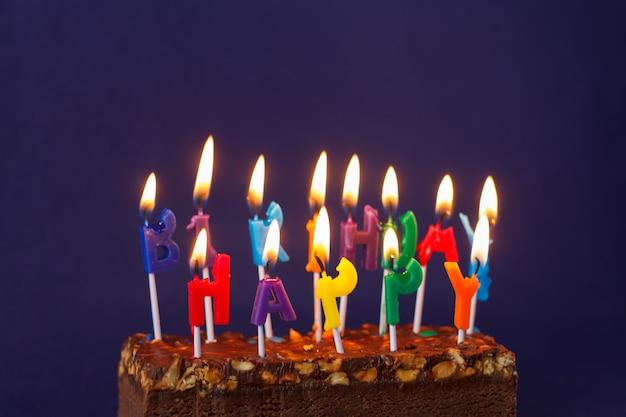 Feliz cumpleaños brownie cake con maní, caramelo salado y coloridas velas encendidas en la superficie violeta. copiar espacio para texto.