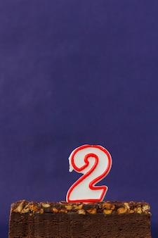 Feliz cumpleaños brownie cake con maní, caramelo salado y velas encendidas en la superficie violeta. copiar espacio para texto. número dos 2