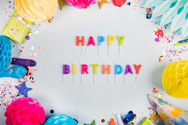 Feliz cumpleaños colorido con artículos decorativos sobre fondo blanco