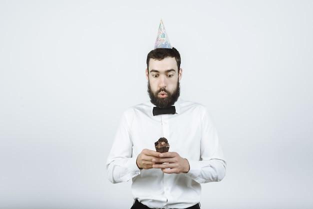 Feliz cumpleaños joven soplando velas de cupcake, pidiendo un deseo