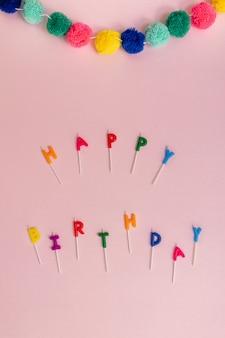 Feliz cumpleaños laicos plana deletreada con velas de colores pastel y guirnalda de pompones sobre un fondo rosa con espacio de copia. maqueta de celebración.