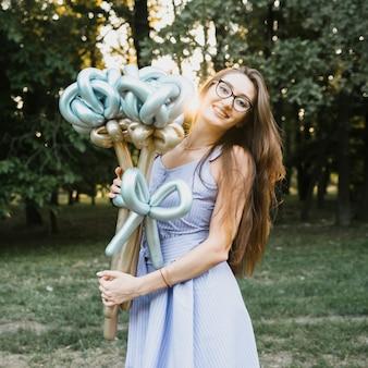 Feliz cumpleaños mujer al aire libre con globos