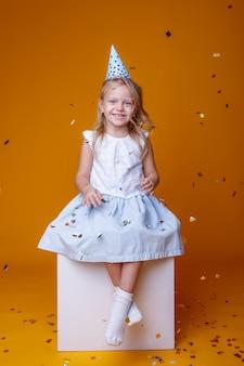 Feliz cumpleaños niña con confeti de colores sobre un fondo amarillo, sentado en un cubo blanco