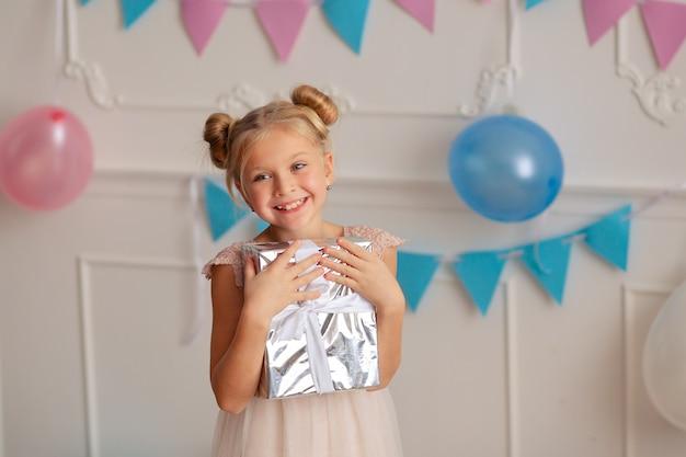 Feliz cumpleaños niña con un regalo en sus manos