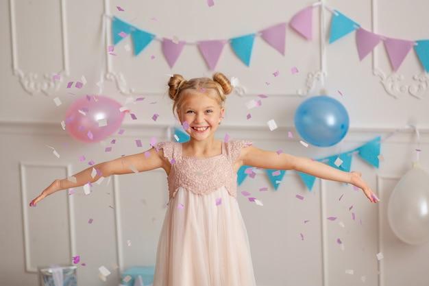 Feliz cumpleaños retrato de una feliz linda rubia de 7-8 años en una decoración festiva con confeti y regalos.