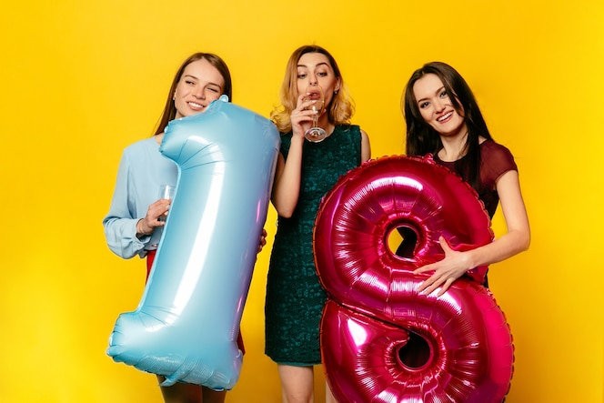 Feliz cumpleaños. tres mujeres bonitas felices en vestido de moda celebrando un aniversario