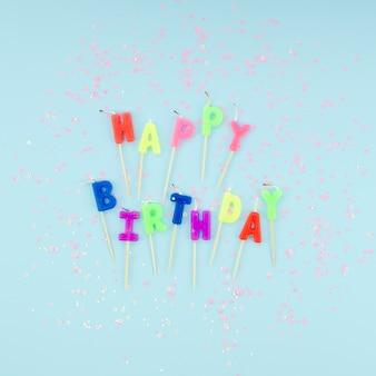 Feliz cumpleaños velas y brillo sobre fondo azul.