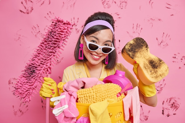 Feliz dama asiática ocupada del servicio de limpieza ocupada ordenando el apartamento equipado con esponja y fregona está sucio rodeado por un montón de ropa sucia usa diadema gafas de sol guantes de goma hace las tareas del hogar