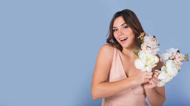 Feliz dama encantadora con flores blancas