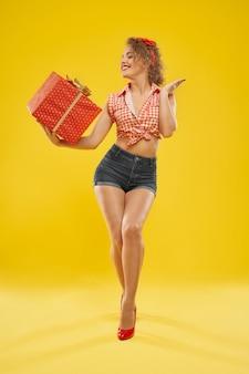 Feliz, delgada chica sosteniendo caja roja con lazo dorado.