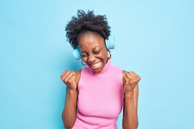 Feliz, despreocupada, modelo femenino de piel oscura hace gesto de sí, bomba de puño celebra el logro del éxito