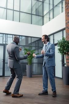 Feliz después de la reunión. hombres de negocios ricos exitosos con trajes elegantes que se sienten felices después de reunirse
