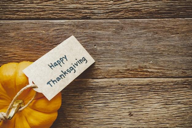 Feliz día de acción de gracias fondo con calabaza y saludo etiqueta en mesa de madera