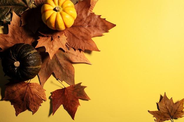 Feliz día de acción de gracias con hojas de arce y calabaza sobre fondo amarillo